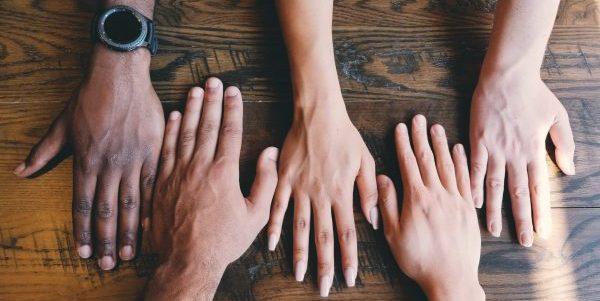 Various Hands reach towards each other on a table